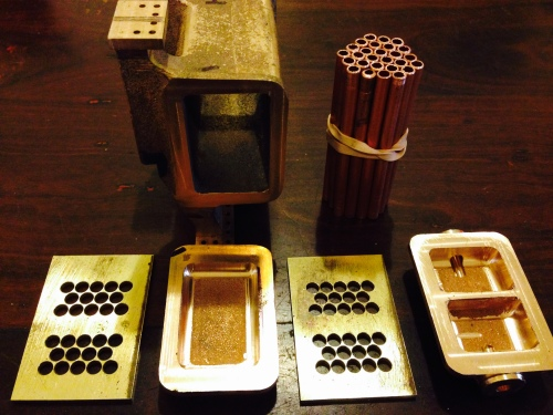 The condenser components.  There are 28 tubes, to be soldered into the holey brass plates.