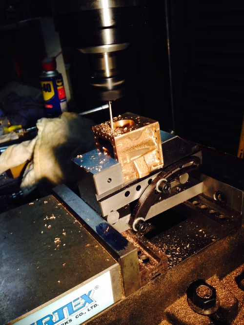 This is the drilling setup. I used a sine vice, sitting on gauge blocks, to produce an exactly 5 degree angle, to avoid the cylinder bore and the bolt holes.  The sine vice was held in the milling vice.